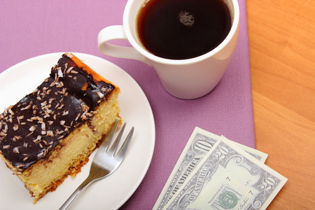 gratuity: Paying for food in the cafe or restaurant, cheesecake and coffee, currencies dollar, finance concept