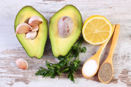 acids: Avocado with ingredients and spices to avocado paste or guacamole, garlic, lemon, parsley, concept of healthy food, nutrition and omega fatty acids