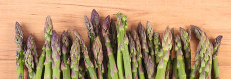 inmunidad: Fresh green asparagus on wooden surface, concept of healthy food, nutrition and strengthening immunity Foto de archivo