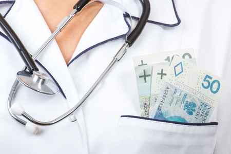doctor money: Woman doctor with stethoscope and polish currency money in apron pocket, paying for medical care, corruption or bribe concept
