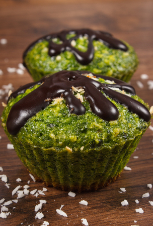 desiccated: Homemade fresh muffins baked with wholemeal flour with spinach, desiccated coconut and chocolate glaze, delicious, healthy dessert or snack