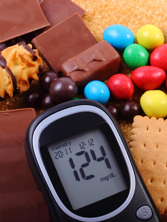 too many: Glucose meter, heap of candies, cookies and brown cane sugar, too many sweets, unhealthy food, concept of diabetes and reduction of eating sweets Stock Photo