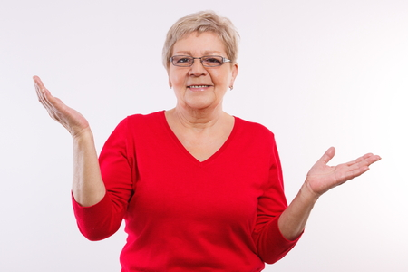 arm: Happy smiling elderly senior woman throwing up her hands and shrugging shoulders, human emotions and gesture, having no clue