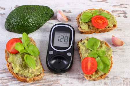 checking ingredients: Glucose meter with result of measurement sugar level and freshly sandwiches with paste of avocado, concept of diabetes, healthy food, nutrition and omega fatty acids