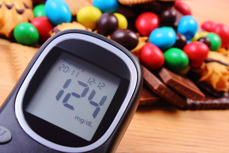 too many: Glucometer with heap of candies and cookies on wooden table, too many sweets, concept of diabetes and reduction of eating sweets Stock Photo