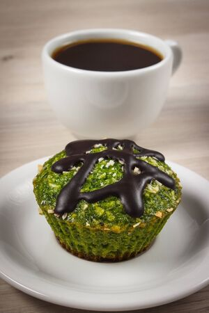 desiccated: Homemade fresh muffins baked with wholemeal flour with spinach, desiccated coconut and chocolate glaze, cup of coffee, delicious, healthy dessert or snack
