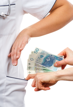 woman doctor: Woman doctor with stethoscope refusing bribes or kickbacks, polish currency money, patient giving money for medical services, concept of corruption Stock Photo