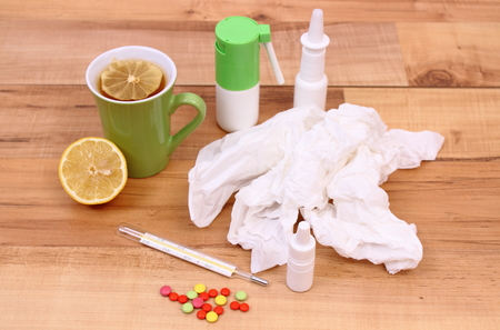 handkerchiefs: Pills and nose drops for colds, used handkerchiefs and hot tea with lemon, treatment of colds, flu and runny