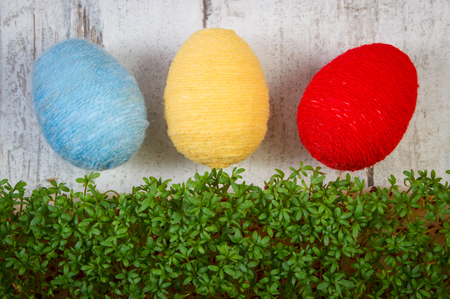 cress: Easter eggs wrapped woolen string and green cuckooflower cress on old wooden background, decoration for Easter