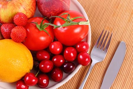 inmunidad: Frutas maduras frescas y verduras que mienten en el plato y cubiertos en superficie de madera, el concepto de la comida sana, la nutrici�n y el fortalecimiento de la inmunidad