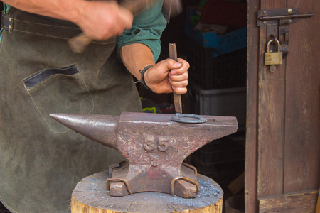 smithy: Blacksmith forges iron horseshoe on the anvil in the smithy