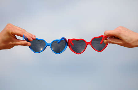 love shape: Hands with red and blue sunglasses shaped heart on sky background