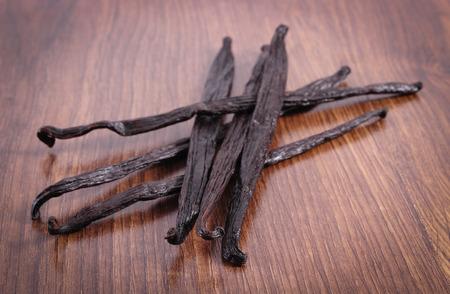 Fresca de vainilla fragante se pega vainas en el tablón de la superficie de madera, el aderezo para cocinar u hornear Foto de archivo