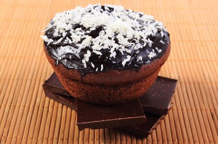 desiccated: Homemade delicious fresh baked chocolate muffins with desiccated coconut lying on pieces of chocolate