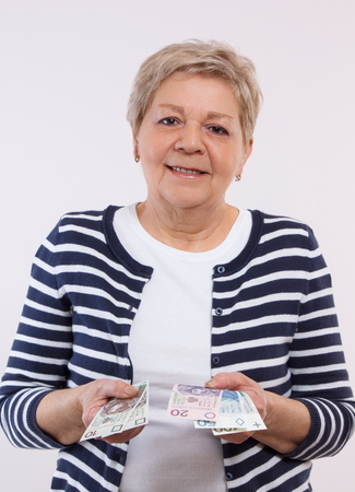 Happy smiling senior woman, an elderly pensioner holding and counting polish currency money, concept of financial security in old age