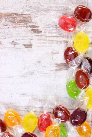 too many: Frame of colorful candies with copy space for text on old white wooden background, too many sweets, concept of reduction of eating sweets
