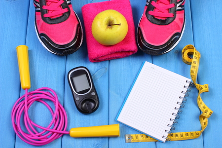 Glucose meter, sport shoes, apple and accessories for fitness, diabetes, healthy and active lifestyles, copy space for text on sheet of paper