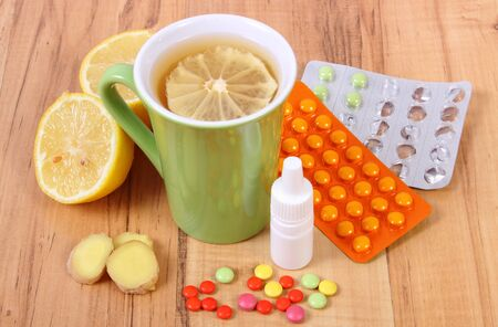 runny: Pills, nose drops and hot tea with lemon and ginger for colds, treatment of colds, flu and runny Stock Photo
