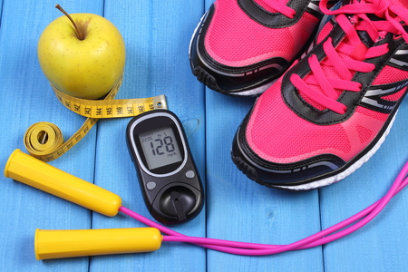 diabetes: medidor de glucosa con el resultado del nivel de azúcar, zapatos de deporte, manzana y accesorios para la aptitud o el deporte, la diabetes, saludable y estilo de vida activo Foto de archivo