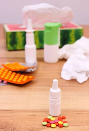 handkerchiefs: Pills and nose drops for colds, used handkerchiefs and other medication in background, treatment of colds, flu and runny Stock Photo