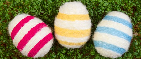 cress: Easter eggs wrapped woolen string and fresh green cuckooflower cress, decoration for Easter