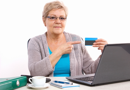 over paying: Senior woman, an elderly pensioner showing credit card, paying over internet for utility bills or online shopping, surfing internet Stock Photo
