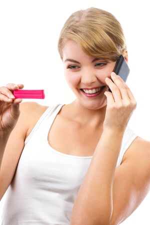 informing: Happy delighted woman looking at pregnancy test and talking on mobile phone, informing someone about positive result test, expecting for baby