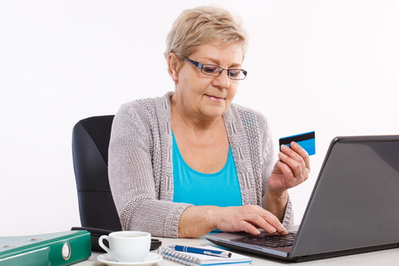 woman sweater: Senior woman, an elderly pensioner with credit card and laptop paying over internet for utility bills or online shopping, surfing internet, typing on computer keyboard Stock Photo