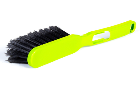 duties: New green brush broom for cleaning on white background, concept of household duties