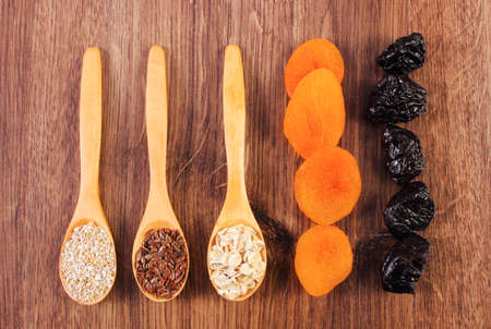 dietary fiber: Portion of linseed, rye flakes and oat bran on spoon with dried fruits, concept of healthy nutrition and increase metabolism, ingredients with dietary fiber Stock Photo