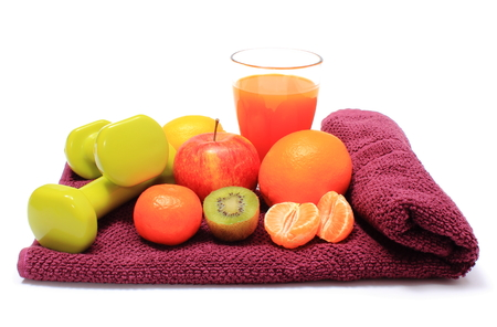 inmunidad: Fresh fruits, glass of juice and green dumbbells for using in fitness lying on purple towel, concept for slimming, healthy nutrition and strengthening immunity