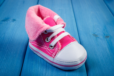 baby shoe: Pair of pink baby shoe on blue boards, concept of extending family and expecting for baby