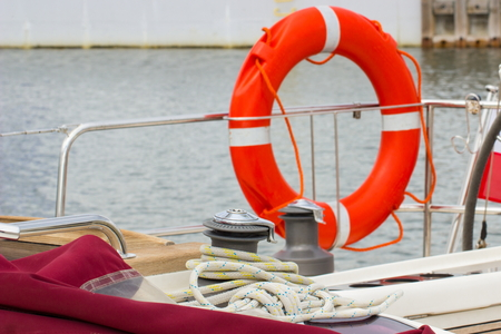 coiled rope: Yachting, colorful coiled rope with orange lifebuoy on deck of sailboat, part of yacht, safety travel
