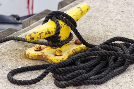 mooring bollard: Yachting, black rope and yellow mooring bollard in port of sailing Stock Photo