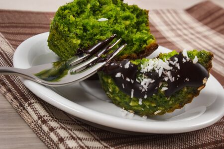desiccated: Homemade muffins baked with wholemeal flour with spinach, desiccated coconut and chocolate glaze, delicious, healthy dessert or snack