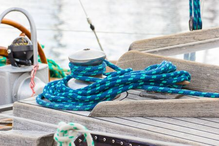 Yachting, wrapped blue rope and bollard on sailboat, details and part of yacht