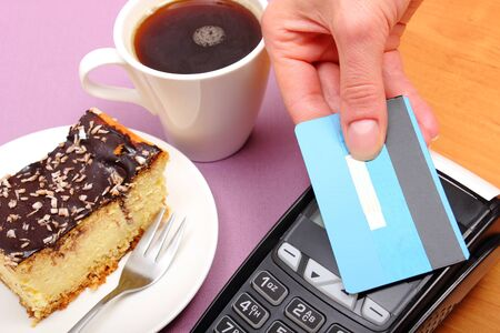 credit card payment: Use payment terminal with contactless credit card with NFC technology for paying in cafe or restaurant, cheesecake and coffee, finance concept