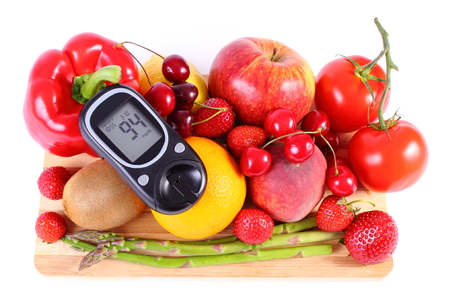inmunidad: Glucometer with fresh ripe fruits and vegetables, concept of diabetes, healthy food, nutrition and strengthening immunity. White background