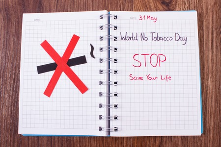 pernicious habit: Red no smoking sign made of paper and inscription world no tobacco day written in notebook, symbol of prohibited smoking, healthy lifestyle without cigarettes Stock Photo