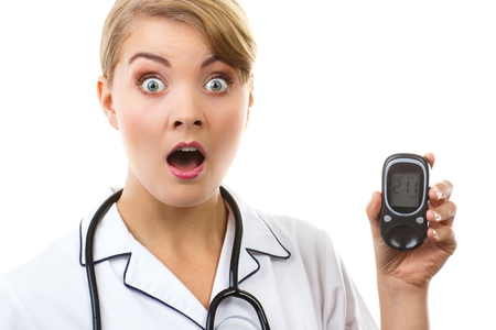 Shocked and worry woman holding glucose meter with bad result of measurement sugar level, concept of diabetes, checking sugar level, white background