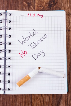 pernicious habit: Broken cigarette and inscription world no tobacco day written in notebook, healthy lifestyle without cigarettes