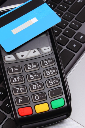 contactless: Payment terminal with contactless credit card and laptop, credit card reader, paying using credit card, finance and banking concept Stock Photo