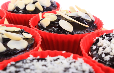 desiccated: Homemade delicious fresh baked chocolate muffins with desiccated coconut and sliced almonds in red silicone cups, concept for dessert