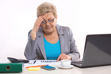 disturbing: Elderly senior business woman holding hand on her head and working at desk in office, analyzing financial charts, business concept, analysis of sales plan, business report