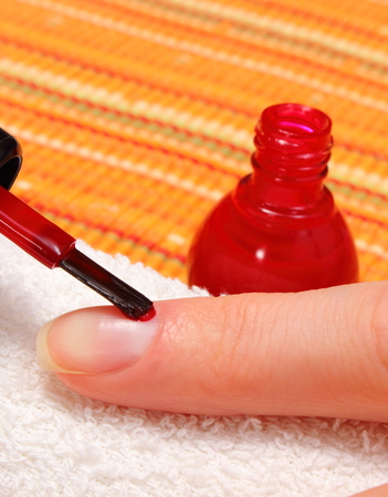 nail polish bottle: Woman applying red nail polish, manicured nails of woman on soft towel, nail care
