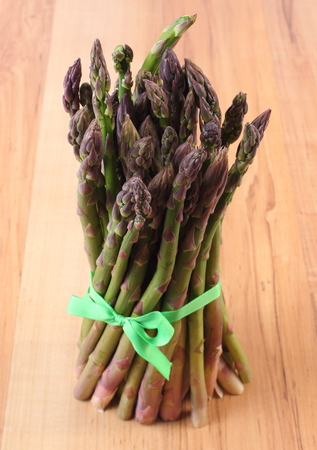 inmunidad: Manojo de esp�rrago verde fresco en superficie de madera, el concepto de la comida sana, la nutrici�n y el fortalecimiento de la inmunidad