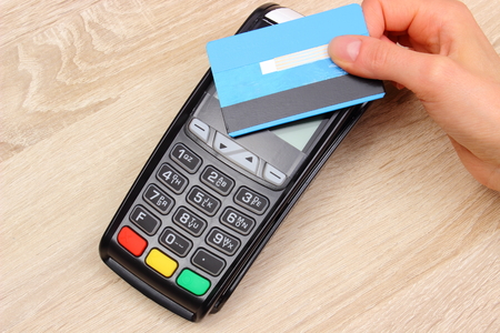 Hand of woman paying with contactless credit card with NFC technology, credit card reader, payment terminal, finance and banking concept Banque d'images