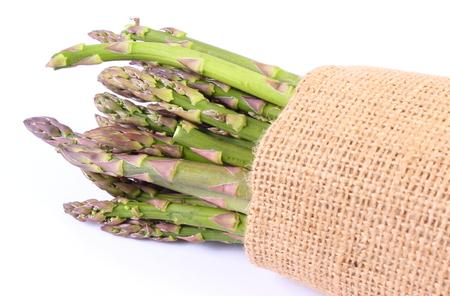 inmunidad: Manojo de cosecha de esp�rrago verde fresco en la bolsa de arpillera, el concepto de la comida sana, la nutrici�n y la inmunidad fortalecimiento. Fondo blanco