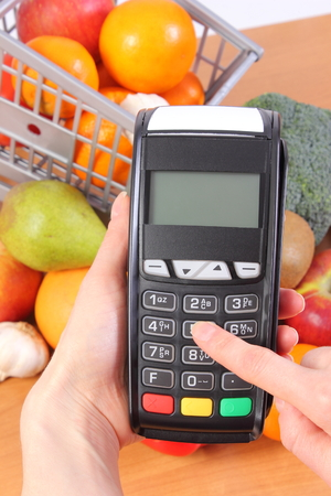 personal identification number: Hand of woman using payment terminal, enter personal identification number, credit card reader and fresh fruits and vegetables with plastic shopping carts, cashless paying for shopping