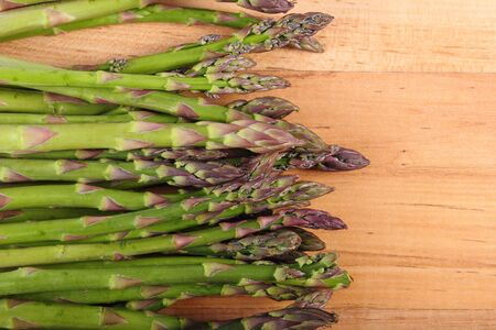 immunity: Fresh green asparagus on wooden surface, concept of healthy food, nutrition and strengthening immunity Stock Photo